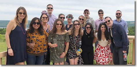 A group of Cornell graduates pose together outside on the Frontenac Point deck.