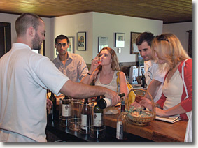 A server pours wine for a group in the tasting room.