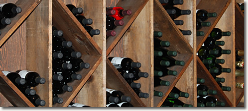 Dozens of wine bottles placed in a wall-mounted wooden wine rack